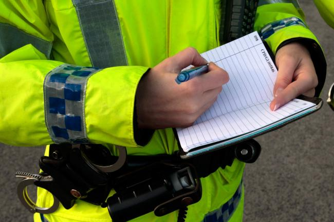 A police officer writes in a notepad